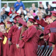 large group of graduates in maroon cap and gown